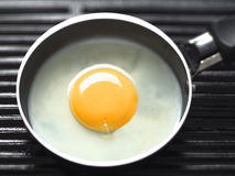 Frying egg on a grill Royalty Free Stock Images