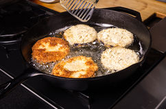 Frying eggplant in cast iron skillet Royalty Free Stock Images