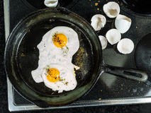 Frying eggs in a cast iron pan Stock Photo