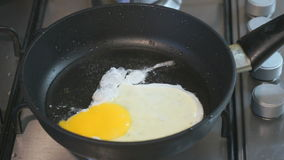 Frying eggs in a skillet. Skillet stands on the hob. Closeup stock footage