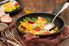 Frying eggs with smoked sausages and vegetables stock image