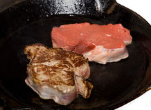 Frying Fillet. Fillet steak in cast-iron pan cooking on hob Stock Photos