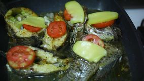 Frying fish in a grill pan with tomatoes, cheese stock video