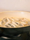 Frying fish in pan Royalty Free Stock Image