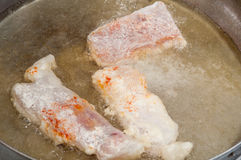 Frying fish rolled in flour and pepper in hot oil.  Stock Image