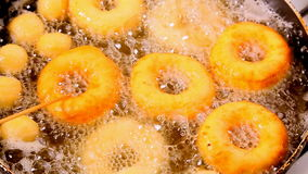Frying fresh donuts on hot oil stock video footage