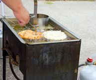Frying Funnel Cake. Deep frying funnel cake in propane fryer outside Royalty Free Stock Images