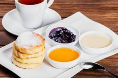 Frying homemade cottage cheese pancakes syrniki with powdered sugar, sour cream, berries jam on plate close up. Traditional Russian cuisine at the Pancake week Stock Image
