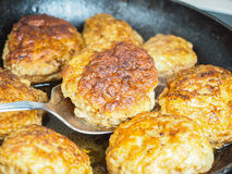 Frying homemade meatballs in black iron pan. In fine broth Royalty Free Stock Photo