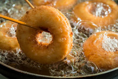 Frying homemade and sweet donuts on fresh oil. Closeup of frying homemade and sweet donuts on fresh oil stock images