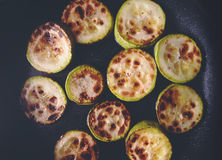 Frying marrows on the black pan. Cut fried marrows on the frying pan Stock Image