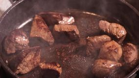 Frying meat on hot pan. Frying beef sirloin in a hot pan. Turning pieces of  beef meat - close-up on top of a kitchen tile. Cook with fork preparing meat stock footage