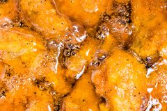 Frying the meat wrapped in breadcrumb on the pan. Close up. Fried chicken in oil Royalty Free Stock Photo