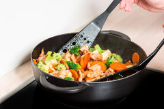 Frying meet and vegies in skillet with hands Royalty Free Stock Photo
