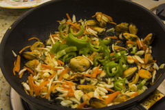 Frying Mussels, calamary and hot pepper. Pan of Moules Mariniere. kitchen recipe concept Royalty Free Stock Photography