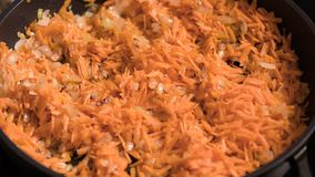 Frying onions and carrots on pan. Chopped onions and carrots fried in vegetable oil in the pan. Close-up on top of a kitchen tile stock video footage
