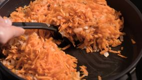 Frying onions and carrots on pan. Chopped onions and carrots fried in vegetable oil in the pan. Close-up on top of a kitchen tile stock footage