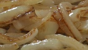 Frying onions in a pan stock video