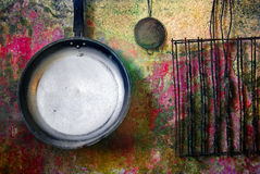 Frying Pan. Strainer and gridiron haged on a rusty wall Royalty Free Stock Photography