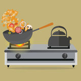 Frying pan cooking stirred vegetable and meat on top of stove Royalty Free Stock Photos