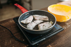 Frying pan with fish slices, seafood cooking Royalty Free Stock Image
