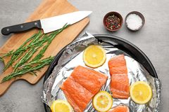 Frying pan with foil, slices of lemon and salmon. On light table Royalty Free Stock Images