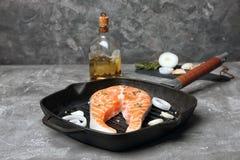 Frying pan with fresh raw salmon steak. On table Stock Photo