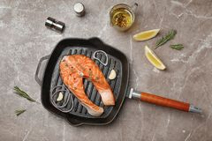 Frying pan with fresh raw salmon steak on table. Top view Stock Photo