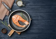 Frying pan with fresh raw salmon steak. On wooden background, top view Stock Photo