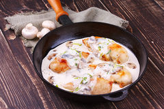 Frying pan with fried chicken breast, mushrooms and greens. Stock Photo