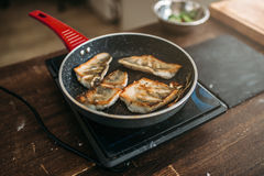 Frying pan with fried fish fillet, seafood cooking. Sea bass slices Stock Photos