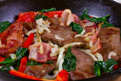 Frying pan with fried meat and bacon Stock Image