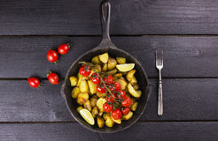 Frying pan with fried potato and the baked cherry tomatoes on br. Anch, lime segments, fresh tomatoes and fork on a wooden brown table - top view Stock Photo