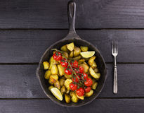 Frying pan with fried potato and the baked cherry tomatoes on br. Anch, segments of lime and fork on a wooden brown table, top view Stock Photos
