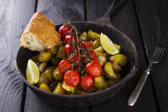 Frying pan with fried potato and the baked cherry tomatoes. On branch, lime segments with piece of bread and fork on a wooden brown table Stock Photo