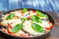 Frying pan with fried tomatoes, zucchini, cheese and herbs stock photos