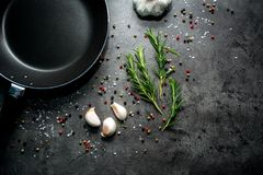 Frying pan with garlic and pepper on black background. stock photography