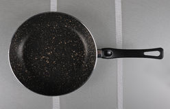 Frying pan on the glass substrate Royalty Free Stock Image