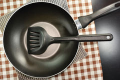 Frying pan and kitchen utensils on table. Stock Images