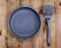 Frying pan and kitchen utensils on wooden table background. View Royalty Free Stock Image