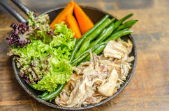 Frying pan with meat, carrots, asparagus and herbs, stands Royalty Free Stock Photography