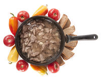 Frying pan with meat and vegetables. Frying pan with meat, tomatoes, pepper lay on a table Stock Photography