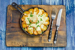 Frying pan with potatoes, cheese and herbs, cutlery royalty free stock images