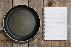 Frying pan and recipe book Stock Images