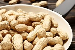Frying pan with roasted peanuts royalty free stock image