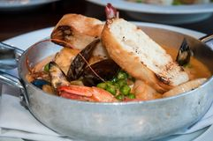 Frying pan with seafood in garlic sauce and toasted bread. Royalty Free Stock Photos