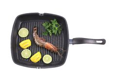 Frying pan with shrimp and lemon slices. Stock Photography