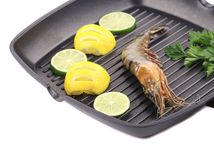 Frying pan with shrimp and lemon slices. Royalty Free Stock Photos