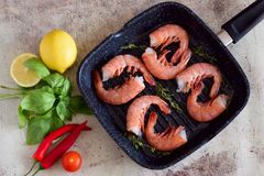 Frying pan with shrimp on the table. royalty free stock images