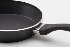 Frying pan. Side view of empty frying pan with teflon coating on white background. The fastening of the handle Stock Image